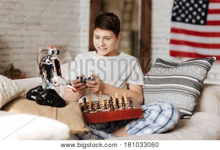 Make a move. Positive delighted man-child using console while controlling his robot, keeping chess-board on the legs