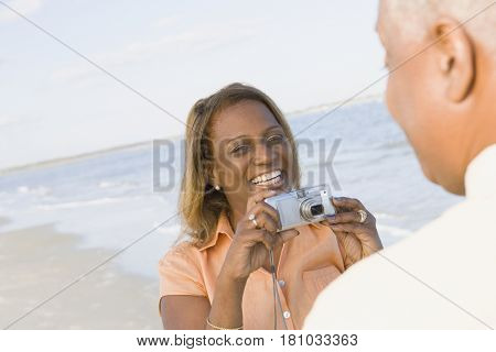 African woman taking husband's photograph