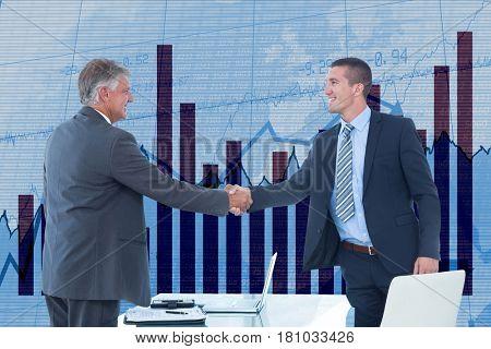 Digital composite of Businessmen shaking hands against graph background