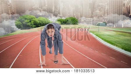 Digital composite of Businesswoman in starting position on tracks