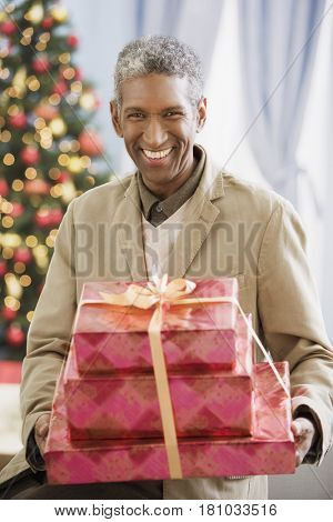 African man holding Christmas gifts