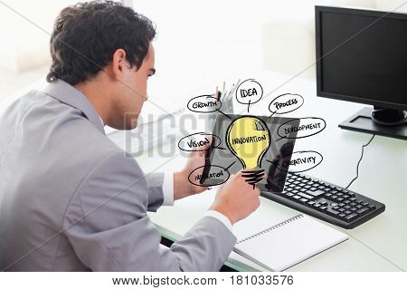 Digital composite of Businessman using tablet PC with various ideas on screen