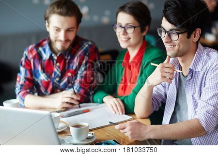 Group of young creative people collaborating at work meeting and smiling looking at laptop screen