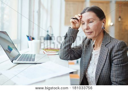 Modern businesswoman with earphones reading contract or resume