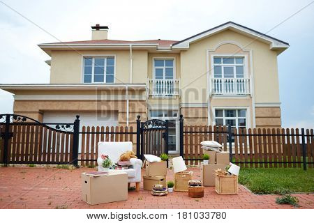 Heap of packed things on asphalt near wooden fence
