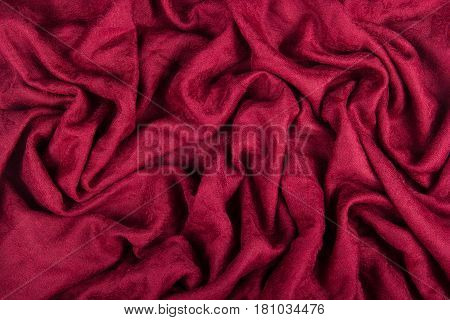 Red woolen fabric with waves. Crumpled fabric. Woolen shawl