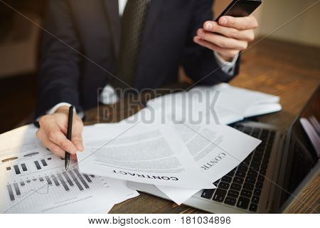 Portrait of busy modern businessman working in office with documentation, contracts and income statistics while using smartphone