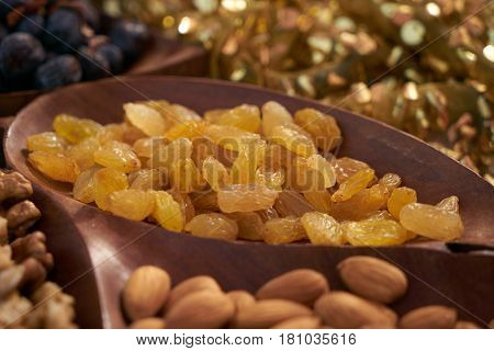 Close-up of yellow raisins in brown wooden bowl.