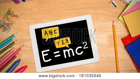 Digital composite of Directly above shot of formula in digital tablet with color pencils and school supplies on wooden ta