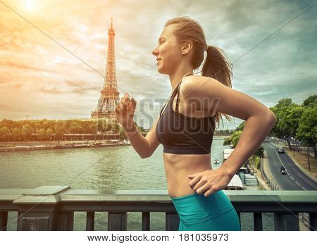 Running woman. Runner jogging at summer day. Female fitness model training outside in Paris City with beautiful view on Eifel Tower - symbol of Paris.