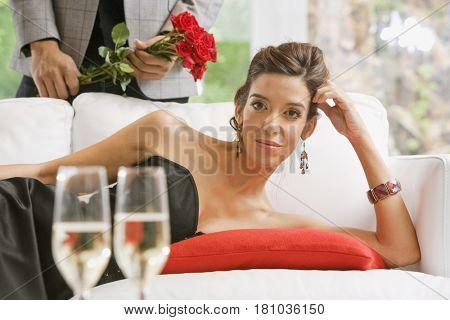 Hispanic woman laying on sofa