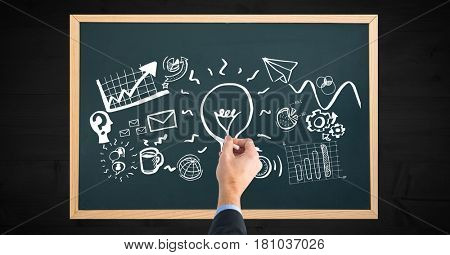 Digital composite of Cropped hand of man drawing on blackboard at wooden table