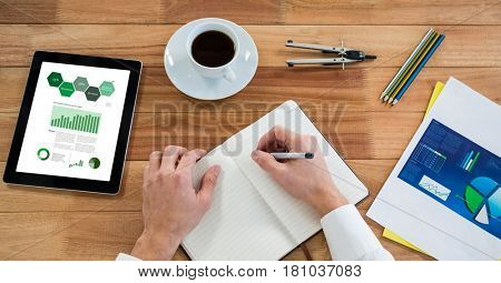 Digital composite of Cropped hand of person writing on diary by graphs in digital tablet at table in office