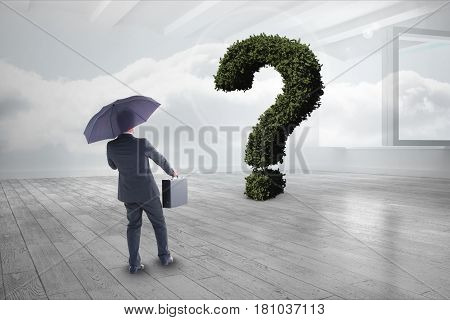 Digital composite of Businessman with umbrella and briefcase looking at question mark made of plants
