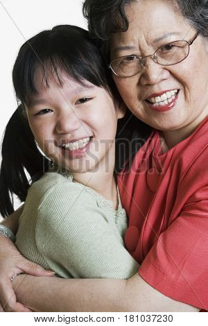 Asian grandmother and granddaughter hugging