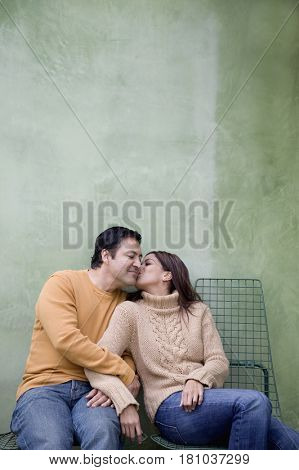 Hispanic woman kissing boyfriend on cheek