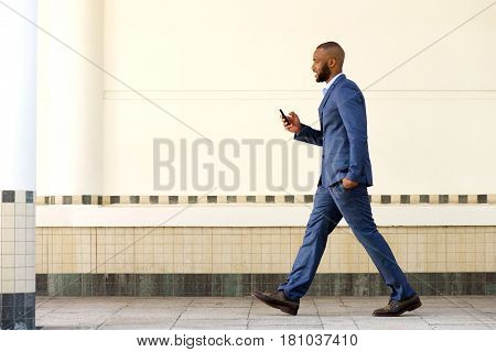 Side Portrait Of Young African Business Man Walking With Mobile Phone