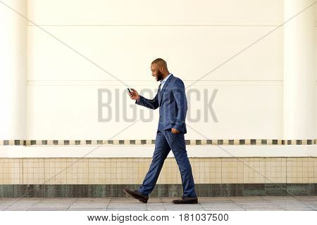 Young Businessman Walking Outdoors And Using Cell Phone