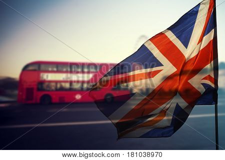 UK flag and red bus at rush hour in London traffic in the background