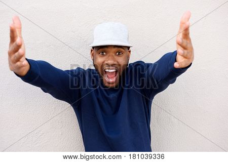 Excited Young African Man With Arms Outstretched And Laughing