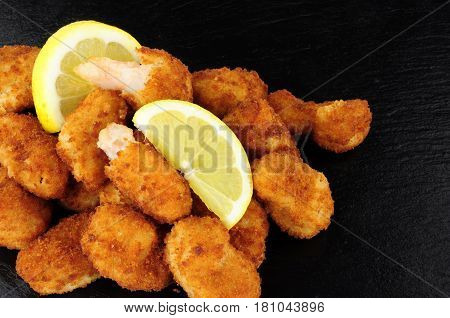 Crispy breadcrumb covered fried scampi on a slate background