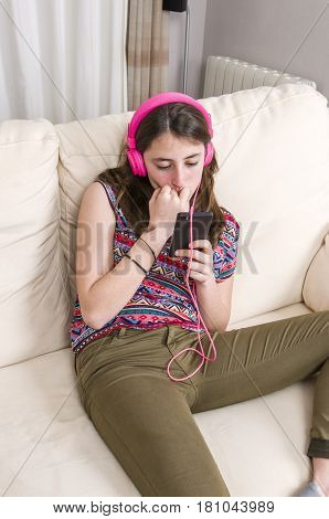 Happy Girl Listening To Music From Mobile Phone Sitting On A Couch At Home