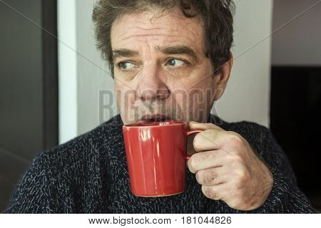 A mature man drinks tea from a red cup