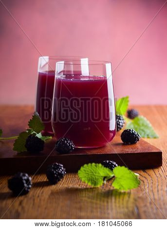 Fresh blackberry juice in glasses with mint and fresh berries on the wooden table.