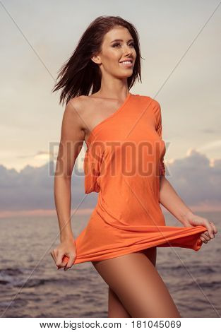 Sensual brunette woman in bright orange dress smiling and posing on the rocks over beautiful sea and sunset sky background