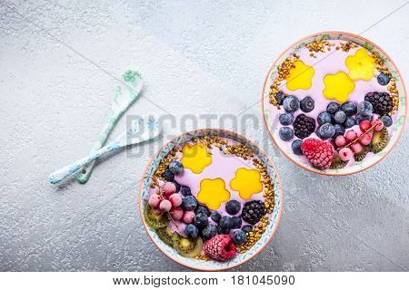 Smoothie in bowls for healthy breakfast. Berry yogurt with blueberries,raspberry,blackberry,red currant, mango, kiwi  and bee pollen over grey background. Top view, copy space