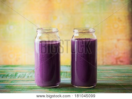 Fresh blackberry and blueberry smoothie in glass bottles