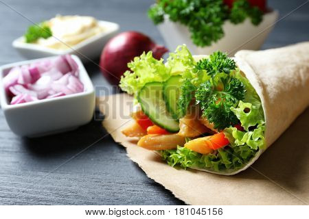 Tasty sandwich with vegetables and meat on grey wooden table