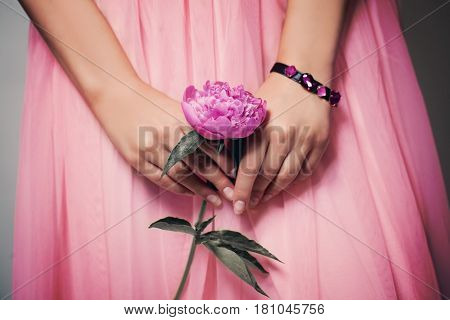 Beautiful Peony Flower in Female Hands on Lacy Prom Skirt. Pink Background