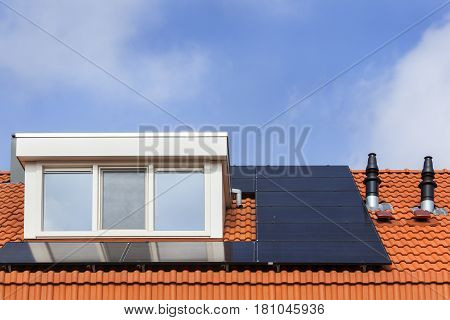 Dormer and solar panels on a red tile roof