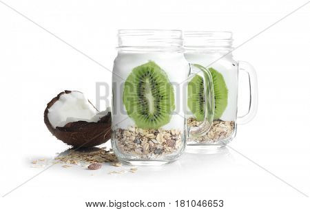 Tasty yogurt dessert with kiwi in mason jars on white background