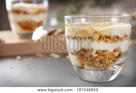 Glass with tasty yogurt dessert on table