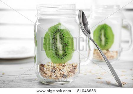 Mason jar with tasty yogurt dessert and kiwi on table