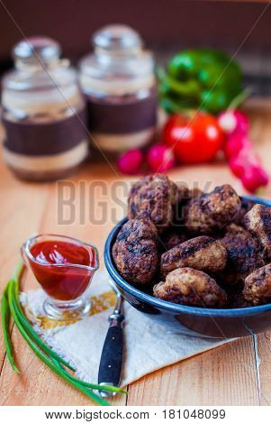 Beef cutlets with ketchup and vegetables. Meatballs with sauce and green onions. Cutlets on a rough wooden table in a rustic style.