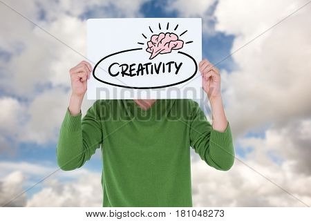Digital composite of Man holding billboard with creativity text while standing against sky