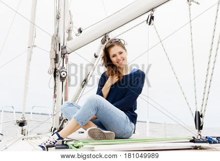 Young, happy, beautiful girl sitting on a deck of a yacht. Traveling, tourism, journey, concept.