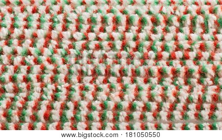 Textured material with pile of green-red-white color
