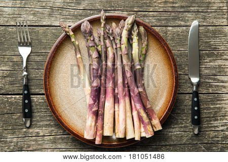 Fresh purple asparagus on plate with cutlery.