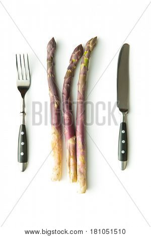 Fresh purple asparagus with cutlery isolated on white background.