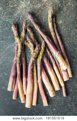 Fresh purple asparagus on old kitchen table.
