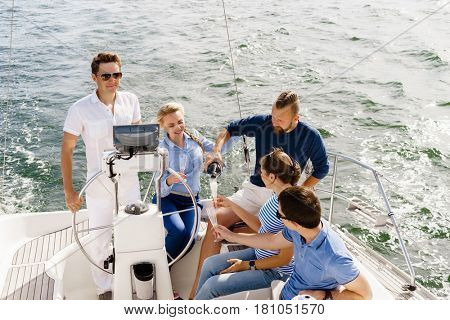 Group of happy friends having a party on a yacht and drinking champagne.  Vacation, holiday, traveling, concept.