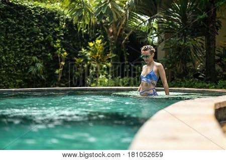 Slim blonde girl in green sunglasses and a blue bikini is relaxing in the swimming pool outdoors on the trees background. She holds her hands in the water and looks downward. Horizontal.