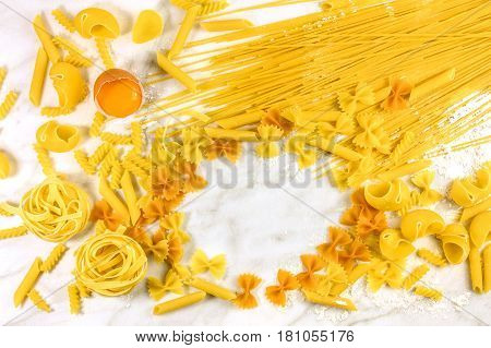 Various types of pasta and an egg on a white marble table with flour, forming a frame for text