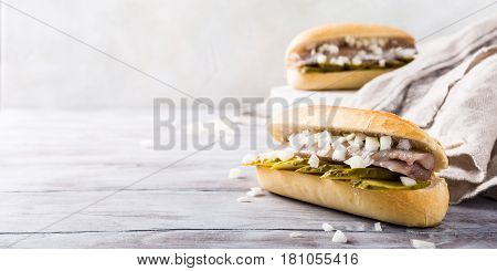 Traditional dutch snack, seafood sandwich with herring, onions and pickled cucumber. Broodje haring. Copy space.