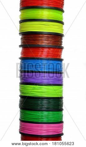 Filament wire for 3D printer close-up. Reels of filament wire for 3D printer different colors. Material produced from FDM printing technology. Many reels vertical view. Isolated on white background
