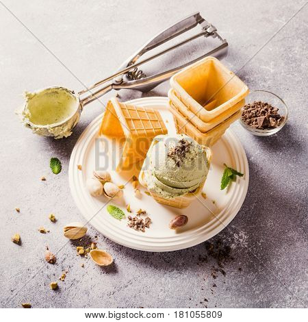 Pistachio ice cream with grated chocolate in waffle cups on gray stone background. Homemade summer food concept. High angle view. Toned.